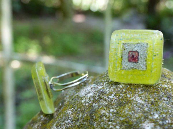 bagues en verre de couleurs verte posées sur pierre
