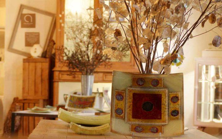 vue de plats en verre avec au fond des bouquets de fleurs séchées